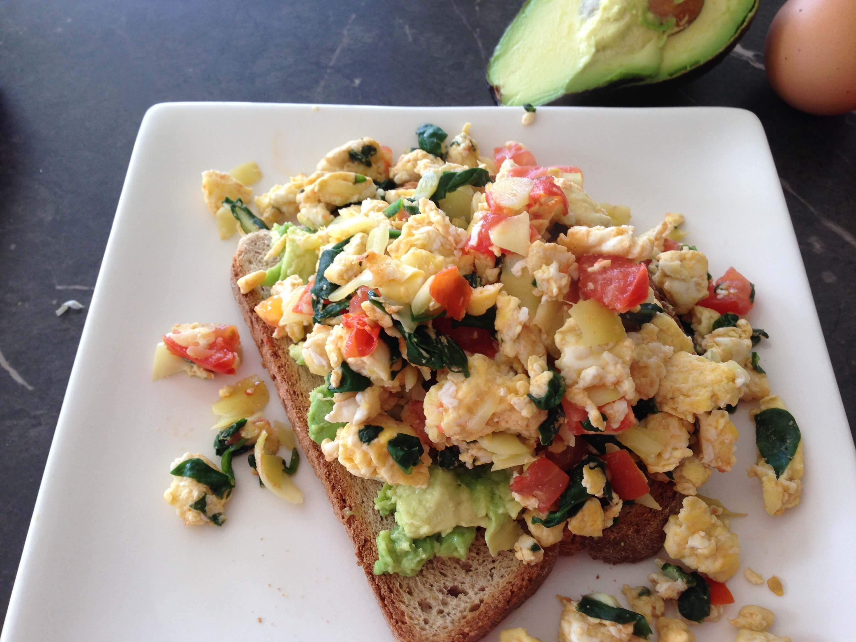 scrambled eggs and veggies on a slice of toast