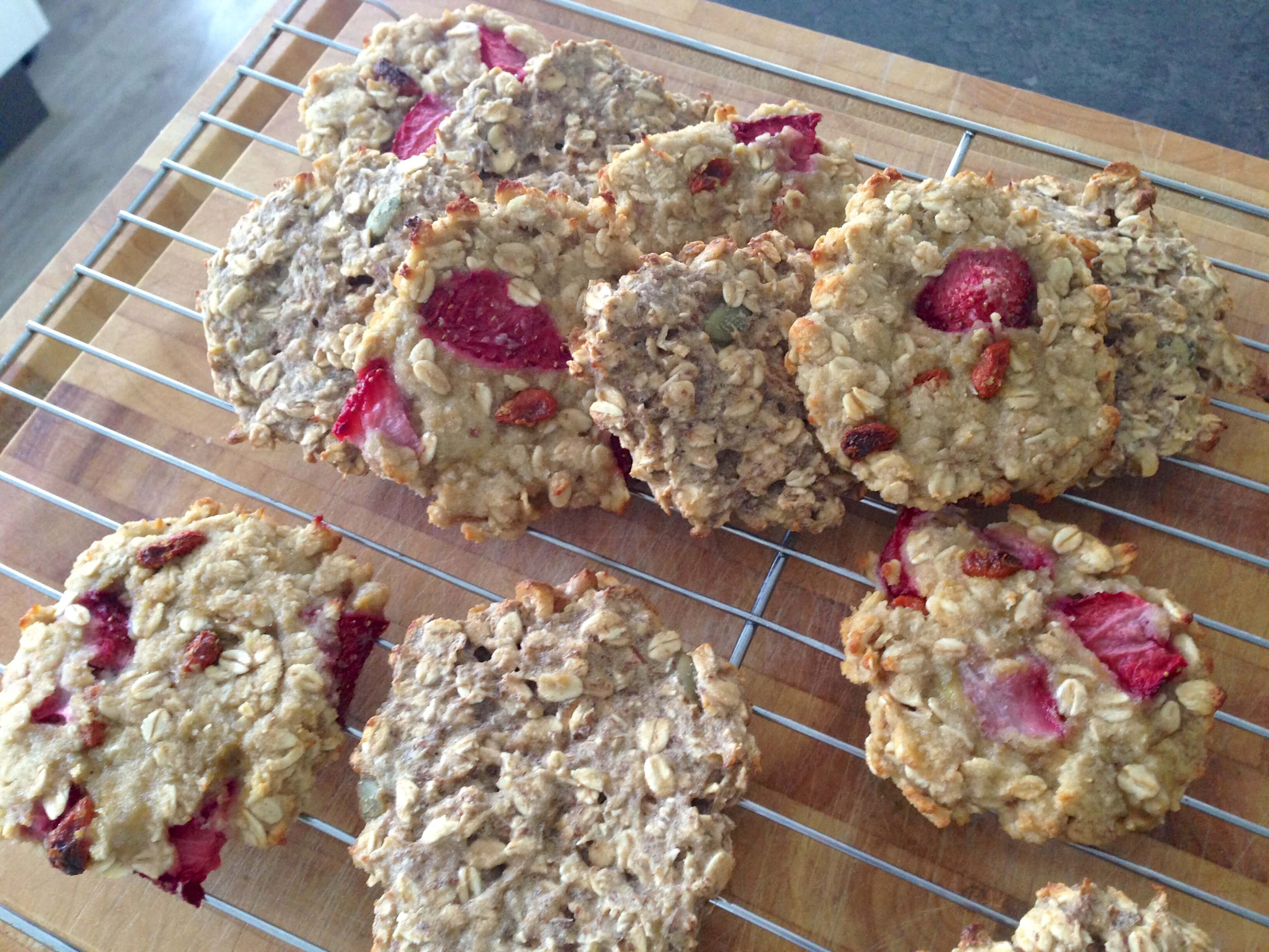 Oat cookies with strawberries and seeds on a cooling rack