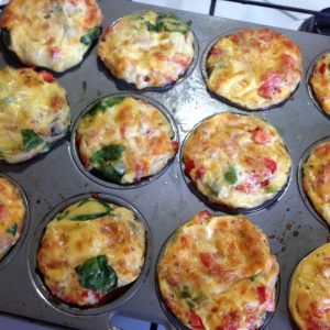 egg muffins in a muffin tin cooling on top of the oven