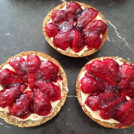 3 individual strawberry tarts sitting on a bench