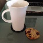 cup of tea and a choc chip cookie next to a computer