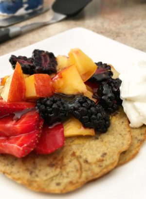close up of pancakes topped with warm, syrupy fruit