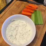 bowl of tzatziki dip on a chopping board with carrot and celery sticks