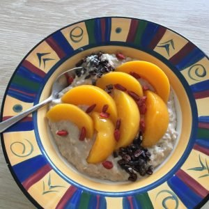 porridge topped with peaches, Goji berries, and cacao nibs