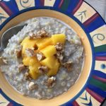 Banana date porridge topped with mango and nuts