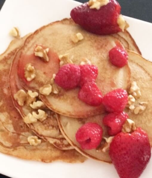 close up of pancakes topped with berries and walnuts