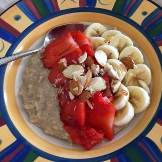 Coconut milk porridge in a bowl topped with strawberries and banana